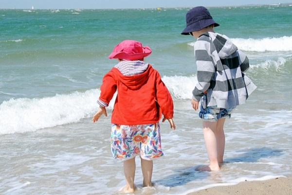 Kinder am Strand zum Meer