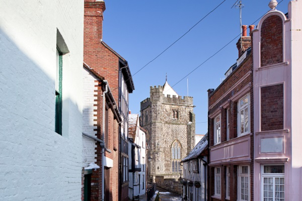 Lane in Hastings Old Town. winter view of street in village with snow and church